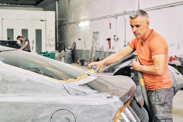 Een monteur die een sportwagen oppoetst
