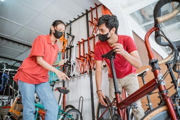 Een monteur en een verkoopster met masker die nieuwe fiets controleren op klant