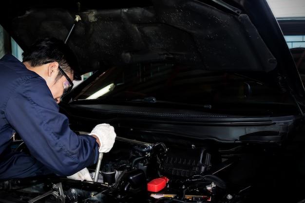 Een monteur gebruik steeksleutel om de motor van een auto in de garage te repareren.