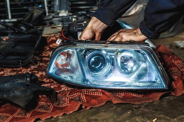 Een monteur in zijn werkplaats repareert een autokoplamp. auto dienstverleningsconcept.