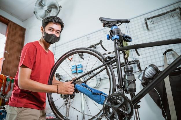 Een monteur met masker aan het werk zet de fietsas vast met een sleutel