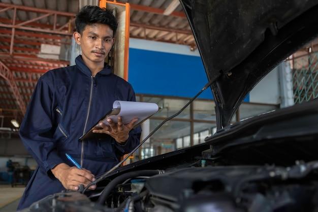 Een monteur service auto in de garage is papieren controleren een lijst auto's.