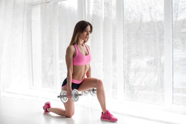 Een mooi atletisch meisje voert oefeningen op de billen uit op een witte achtergrond. fitness