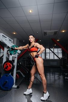 Een mooi, atletisch sexy meisje traint en doet fitness in de sportschool. fitness, bodybuilding.