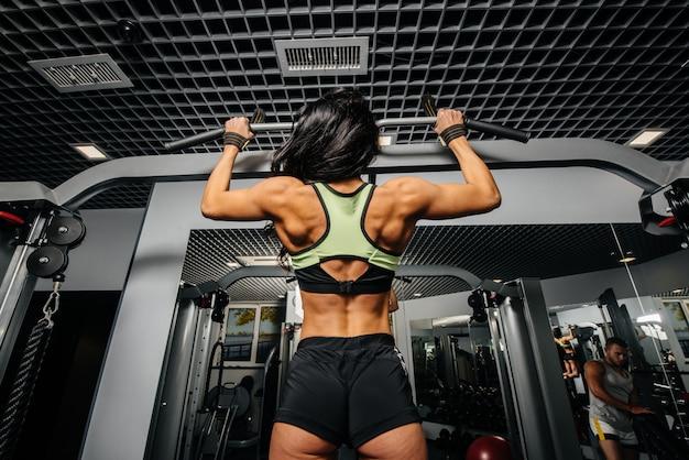 Een mooi, atletisch sexy meisje trekt omhoog in de sportschool. fitness, bodybuilding
