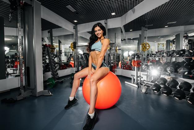 Een mooi, atletisch sexy meisje zit op een bal na fitnesslessen in de sportschool. fitness, bodybuilding.