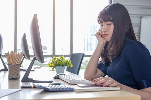 Een mooi aziatisch meisje dat een donkerblauw kostuum draagt, zit aan een bureau in een modern kantoor en werkt stress