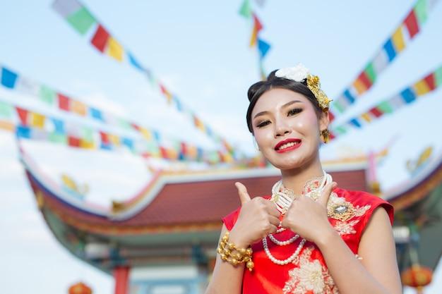 Een mooi aziatisch meisje dat een rood kostuum draagt