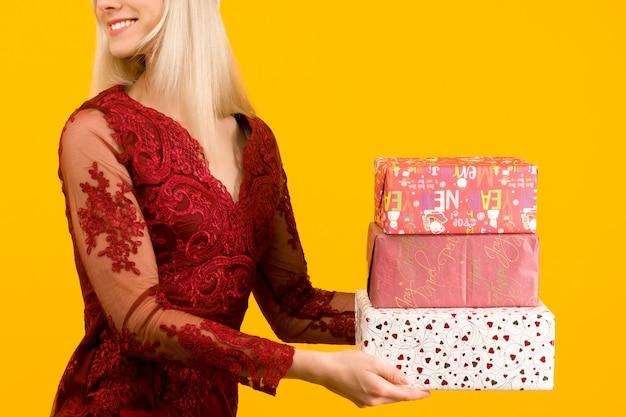 Een mooi aziatisch meisje in een rode jurk houdt in handen geschenken op gele achtergrond