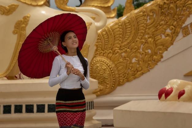 Een mooi birmaans meisje dat een nationaal kostuum draagt voor een wandeling, binnen de shwedagon-pagode van yangon, myanmar.