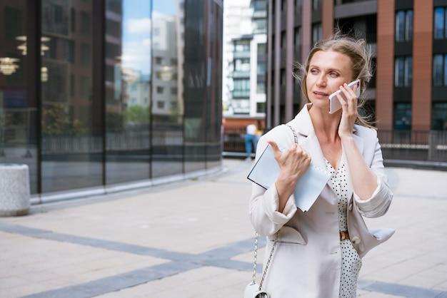 Een mooi blond meisje houdt een smartphone en een notitieboekje in haar handen zakenvrouw gebruikt een mobiele telefoon
