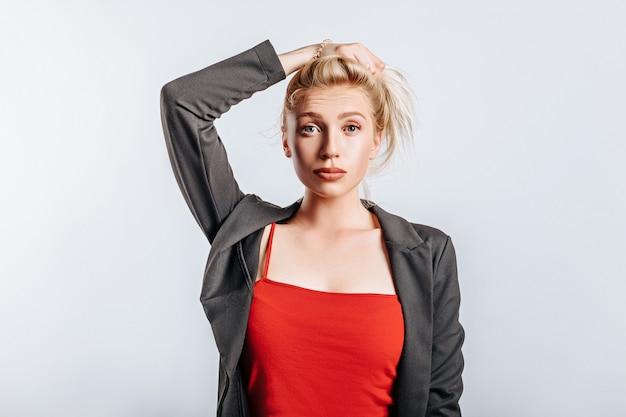 Een mooi blond meisje houdt haar haar vast en maakt haar eigen kapsel met de emotie van verrassing. vrouw in zwarte jas en rode bovenkant op grijze geïsoleerde achtergrond voor reclame. neuspiercing