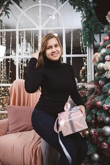 Een mooi blond meisje in een zwarte trui zit in de buurt van een nieuwjaarsboom met een cadeau in haar handen.