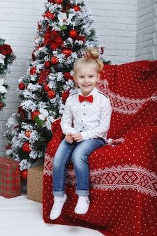 Een mooi blond meisje in jeans en wit overhemd zit in de buurt van de kerstboom.