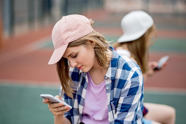 Een mooi blond meisje met een geruit hemd en een pet zit op het sportveld met een telefoon