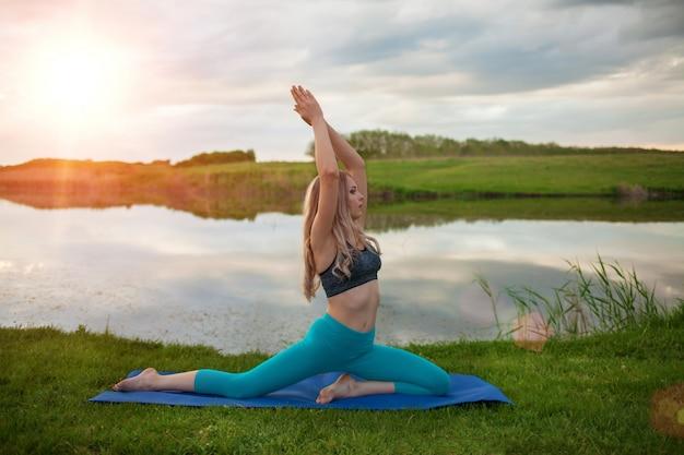 Een mooi blond meisje oefent yoga op het meer bij zonsondergang uit. close-up het ondersteunt een gezonde levensstijl