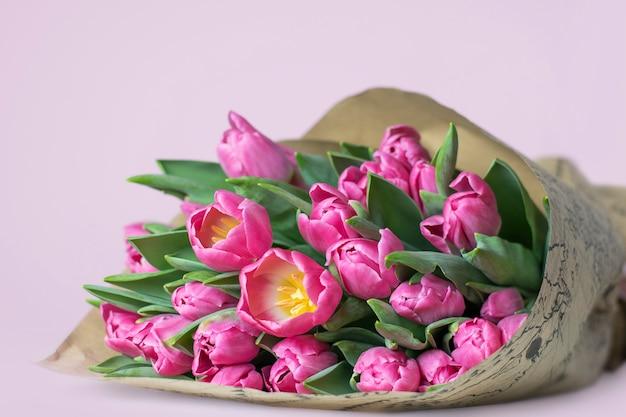 Een mooi boeket van roze tulpen op een roze achtergrond