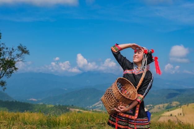 Een mooi boerenmeisje met stro in rijstvelden in noord-thailand.