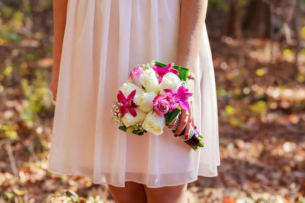 Een mooi bruidsboeket van paars, roze en witte greep door een bruid