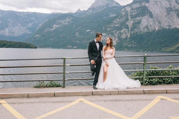 Een mooi bruidspaar loopt op een achtergrond een meer en bergen in een fee hallstatt