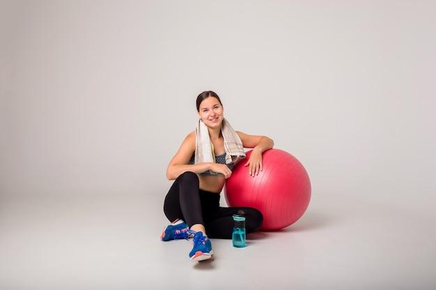 Een mooi donkerbruin meisje in een sportuniform zit met een grote rode fitnessbal op een wit geïsoleerd met ruimte voor tekst