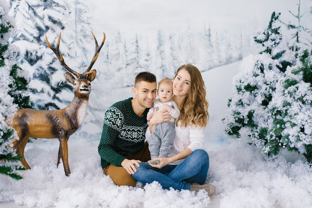 Een mooi en gelukkig gezin van jonge ouders en een baby in wintertruien in een nep winterbos, in de fotozone in de studio