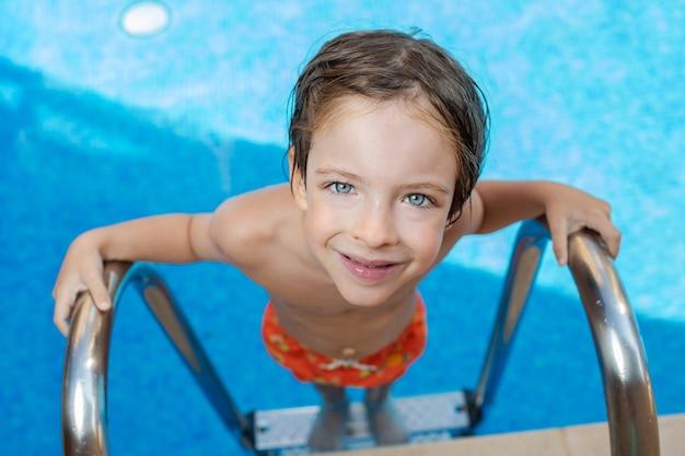 Een mooi en schattig jongetje met nat haar stapt uit het zwembad. een vijfjarig kind met blauwe ogen zwemt op een zomerse dag in het zwembad