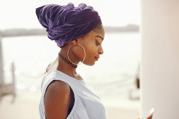 Een mooi en stijlvol meisje met donkere huid loopt in een zonnige zomerstad