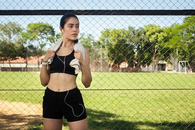 Een mooi fitness meisje luistert naar muziek op haar koptelefoon in het park