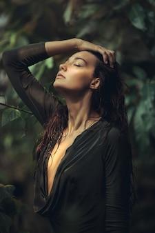 Een mooi gebruind meisje met natuurlijke make-up en nat haar dat in de jungle staat
