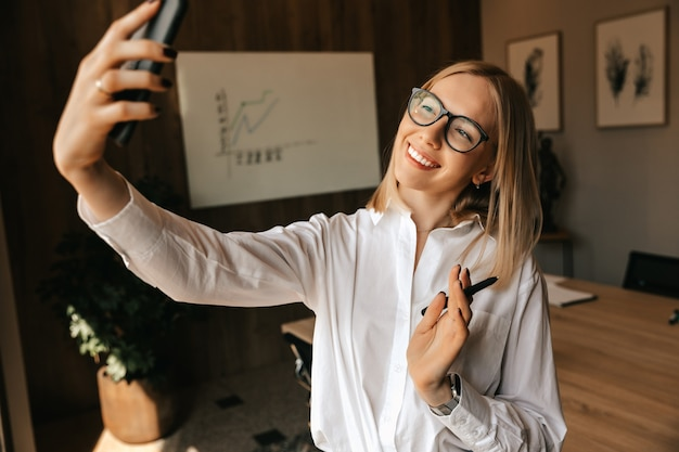 Een mooi, gelukkig blond meisje zendt een live gesprek uit via de telefoon