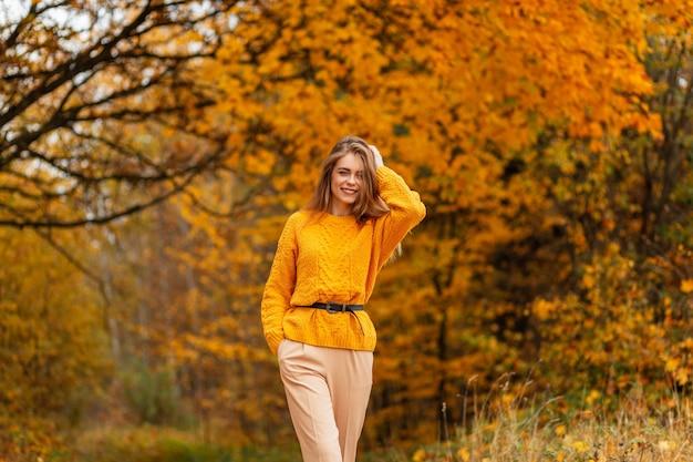 Een mooi, gelukkig, kaukasisch meisje met een glimlach in een modieuze vintage gele trui loopt in een herfstpark met felgekleurd gebladerte