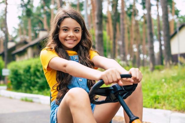 Een mooi gelukkig klein meisje op vakantie rijdt op een fiets en heeft plezier in het bos zomerkamp