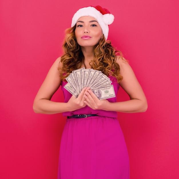 Een mooi geschokt sexy meisje in een nieuwjaarshoed, houdt geld in handen. viering van kerstmis of nieuwjaar