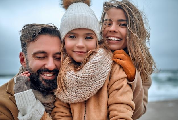 Een mooi getrouwd stel en hun lieve dochter knuffelen aan de kust, gekleed in jassen in de winter.