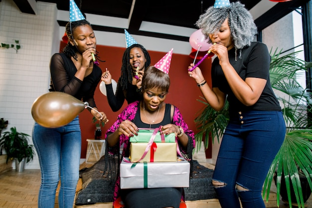 Een mooi glimlachend afrikaans meisje opent een cadeau op haar verjaardagsfeestje. gelukkige afrikaanse meisjes in feestmutsen en met blazende hoorns staan rond feestvarken en glimlachen