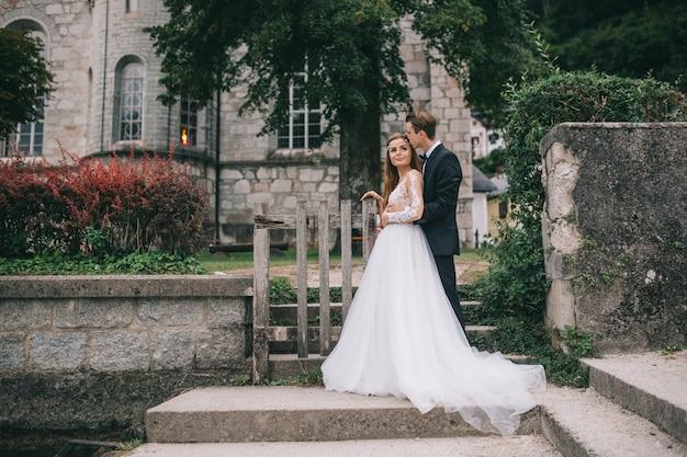 Een mooi huwelijkspaar stellen op een oude kathedraal als achtergrond in een fee oostenrijkse stad