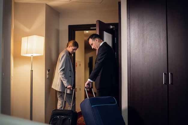 Een mooi jong bedrijfspaar dat hun hotelkamer met de koffers verlaat