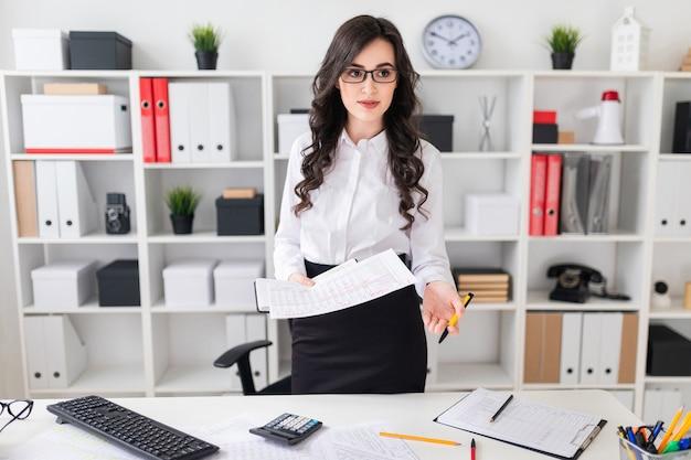 Een mooi jong meisje bevindt zich dichtbij een bureau en houdt een pen en een notitieboekje in haar handen het meisje onderhandelt