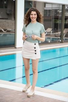 Een mooi jong meisje dat zich dichtbij een pool bevindt