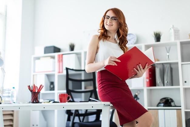 Een mooi jong meisje ging op de tafel in het kantoor zitten en hield een rode map vast.