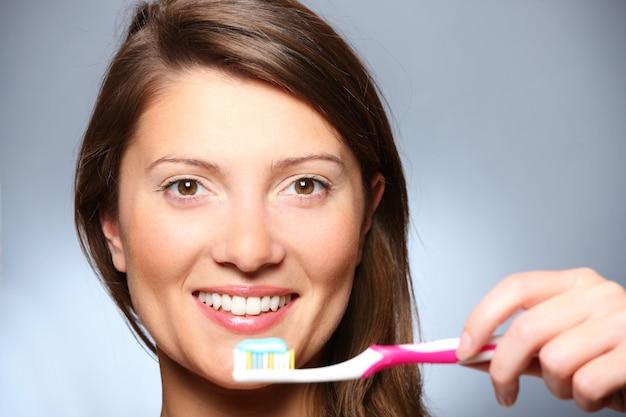 Een mooi jong meisje haar tanden poetsen over grijze achtergrond