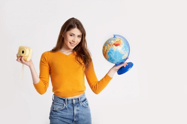 Een mooi jong meisje in een gele trui houdt een wereldbol en een camera. recreatie, reizen, toerisme. ruimte voor tekst