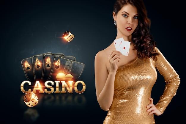 Een mooi jong meisje in een gouden jurk heeft speelkaarten in haar handen