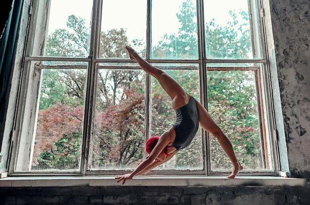 Een mooi jong meisje in een grijs zwempak staat op haar handen op een vensterbank in touw. yoga-concept. turnster die oefeningen doet.