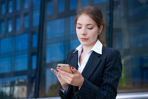 Een mooi jong meisje in een modieus zwart jasje en een wit overhemd staat op straat en houdt een telefoon in haar handen. tegen de achtergrond van een kantoorgebouw