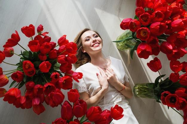 Een mooi jong meisje in een peignoir ligt op de grond tussen grote boeketten tulpen. 8 maart concept.