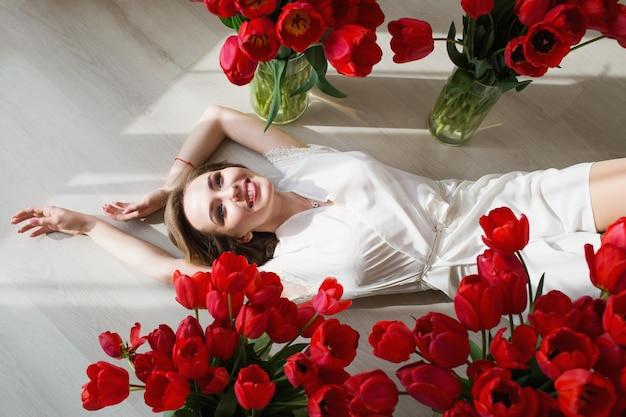 Een mooi jong meisje in een peignoir ligt op de grond tussen grote boeketten tulpen