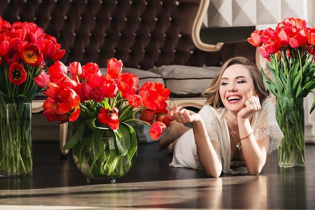 Een mooi jong meisje in een peignoir ligt op de vloer in de studio met boeketten tulpen. het concept van 8 maart. ochtend van de bruid.