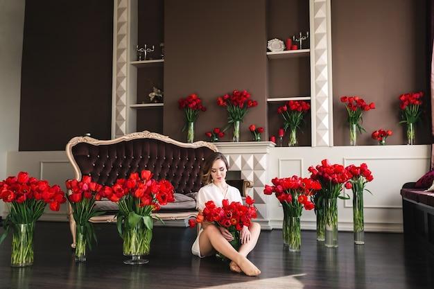 Een mooi jong meisje in een peignoir zit op de grond in de woonkamer tussen grote boeketten tulpen. concept 8 maart.